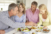 Mid age couples enjoying meal at home — Stockfoto