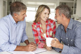 Mid age couple with financial advisor at home — Stock Photo