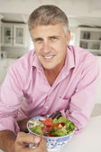 Mid age man eating salad — Stock Photo