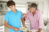 Father making teenage son do housework — Stock Photo