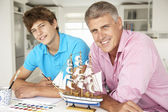 Father and teenage son model making and painting — Stock Photo
