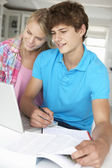 Teenage boy and girl doing homework with laptop — Stock Photo