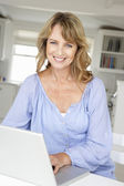 Mid age woman using laptop — Stock Photo