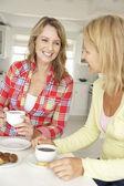 Meados de idade mulheres conversando sobre o café em casa — Foto Stock