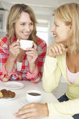 Mid age women chatting over coffee at home — ストック写真