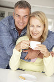 Mid age couple with coffee at home — Stock Photo