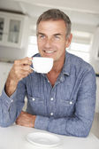 Mid age man with coffee at home — Stock Photo