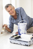 Senior man decorating house — Foto Stock
