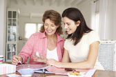 Adult mother and daughter scrapbooking — Stock Photo