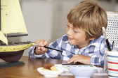 Young boy making model ship — Stock Photo
