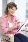 Senior woman sketching — Stock Photo