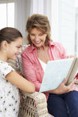 Senior woman and granddaughter with photo album — Foto Stock