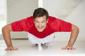 Man doing push-ups in home gym — Stock Photo