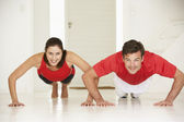 Couple doing push-ups in home gym — Stok fotoğraf