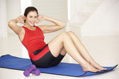Woman doing sit-ups in home gym — Stock Photo