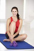 Woman sitting on exercise mat — Stock Photo