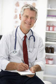 Senior doctor writing prescription — Stock Photo