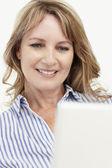 Połowie wieku kobieta korzysta z laptopa — Zdjęcie stockowe