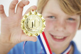 Young boy showing off medal — Stock Photo
