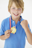 Young boy showing off medal — Стоковое фото