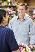 Man serving customer in florist — Stock Photo