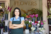 žena stojící mimo květinářství — Stock fotografie