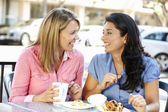 Women chatting over coffee and cakes — Stock Photo