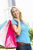 Woman carrying shopping bags in city park — Stock Photo