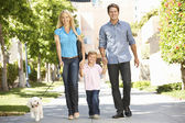 Family walking with dog in city street — Stok fotoğraf