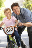 Father with boy on bike — Stock Photo