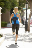 Femme qui court sur la rue de la ville — Photo