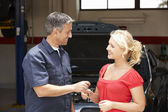 Young woman collecting care from repair shop — Stock Photo
