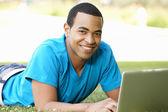 Joven usando laptop al aire libre — Foto de Stock