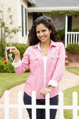 Young Hispanic woman outside new home — Stock Photo
