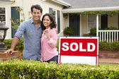 Hispanic couple outside home with sold sign — Foto Stock