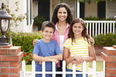 Mother and children outside home — Stock Photo