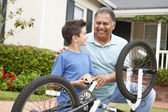 Boy and grandfather fixing bike — Stock Photo