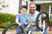 Boy and grandfather fixing bike — Stok fotoğraf