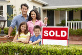 Hispanic family outside home with sold sign — Stock Photo