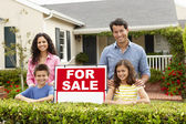 Hispanic family outside home with for sale sign — Stock Photo