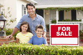 Father and children outside home for sale — Stock Photo