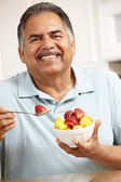 Senior man eating fruit — Stock Photo