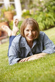 Mid age woman relaxing in garden — Stock Photo