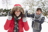 Young couple having snowball fight — Stock Photo