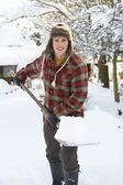 Young man clearing snow — Stockfoto