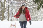 Young woman in snow with sledge — Stock Photo