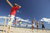 Teenagers playing cricket on beach — Stock Photo