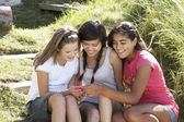 Teenage girls using phone outdoors — Stock Photo