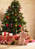 Little girl with parcels round Christmas tree — Zdjęcie stockowe