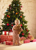 Little girl with parcels round Christmas tree — Stok fotoğraf